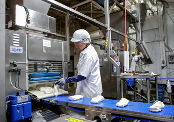 An employee checks on a dough during the production process at the Gonnella Baking Company in Aurora