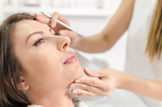 Woman in beauty salon on examination face skin