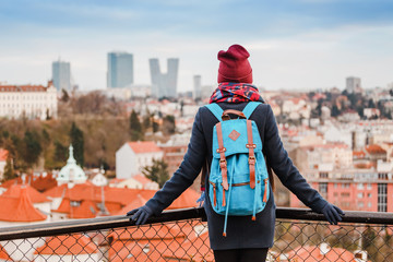 Woman tourist in a coat with a backpack travels in the city park of Prague, rear view