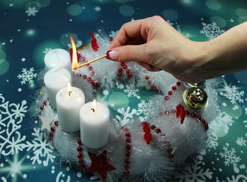 Third Advent Sunday/ candles on an advent wreath/ A woman fires the third candle on an advent wreath.