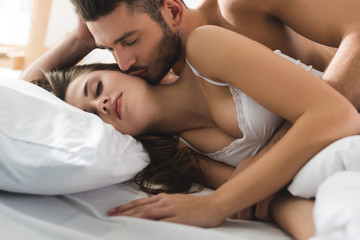 young man embracing and kissing his girlfriend from behind in bed