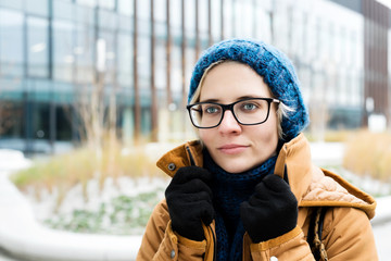 Winter outdoor portrait of a beautiful young blonde woman with grey eyes in black glasses in a dark blue hat with scarf and knitted gloves in Europe stylish modern city centre