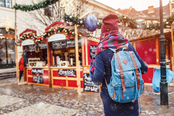 Rear view of tourist woman with backpack choosing Christmas decoration souvenirs and gifts at the advent market
