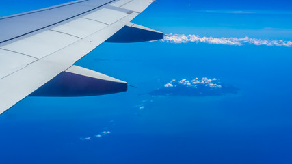 Wing of airplane with blue sky, cloud, island and sea.