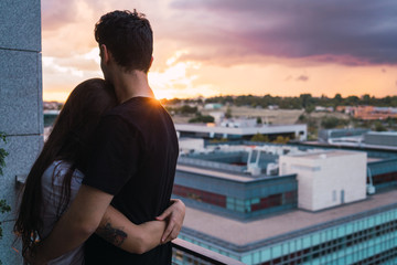 Couple cuddling on balcony