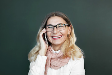 Senior people, modern technologies and electronic devices concept. Charismatic middle aged European woman in glasses grinning broadly while laughing at joke, speaking on phone to her friend