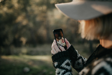 Woman taking a photo with a mobile phone in nature. She appears in the screen through the device frontal camera.