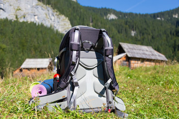 Backpack and yoga mats on mountain meadow with traditional wooden shepherd's huts, Alps, Slovenia.