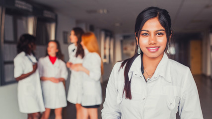 Asian girl student medical worker, wearing a white robe, against a multinational group of girlfriends, with a beautiful smile. Hospital Units in the Background Health Future 2018