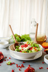 Seasonal salad with persimmon, pomegranate and dressing from honey and mustard