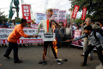 Activists of the Socialist Unity Centre of India (SUCI) burn an effigy depicting U.S. President Donald Trump during a protest against the U.S. decision to recognize Jerusalem as the capital of Israel, in Kolkata