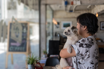 Asian woman and dog in coffee shop cafe