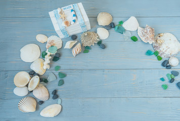 Sea, beach saver, background, postcard. the mood of rest, vacation. Shells of stone pebbles and a white chest on a gentle light blue wooden background.