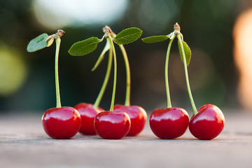 Red cherries berry with green leaves. Ripe fruit macro view photo. Selective focus, shallow depth of field. Beautiful bokeh background