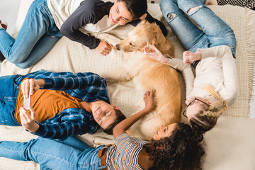 overhead view of multiethnic teenagers lying on bed and taking selfie with dog