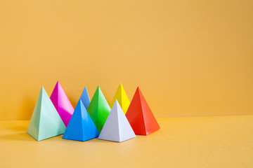 Minimalist design colorful abstract geometrical composition. Three-dimensional prism pyramid rectangular objects, orange background. Gray blue pink red violet green colored solid figures, soft focus