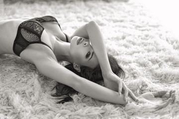 Passionate brunette woman in bra posing on carpet black and white