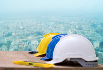 safety helmet with cunstruction objects and on table with city scapes.