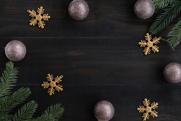 Top view of  luxury christmas ornaments  glittering ball , gold snowflake and ,pine brance on black wood table top,Flat lay , holiday celebration still life,mock up for adding text,copy space