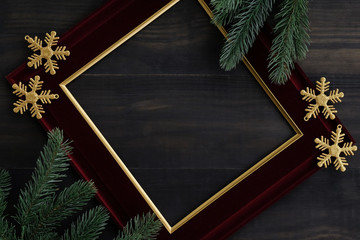 Top view of  blank red luxury flame with christmas ornament, gold snowflake  ,pine brance on black wood table top,Flat lay , holiday celebration still life,mock up for adding text,copy space.
