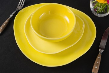 Table setting with yellow bowl and plates