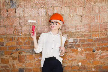 Portrait of architect student or painter with paint roller and protect helmet wearing. Brick red background.