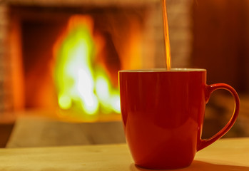 Mug; of tea; on wooden table; before; cozy  fireplace; background, soft focus.