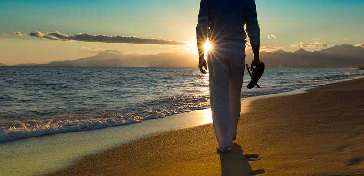 Young sexy man is walking bare foot on a beautiful sunset beach at the ocean. stand in water and holding his flip flops in his hands. mountain range blue sky and water