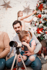 Image of parents and daughters with telescope on background of decorated New Year's fir