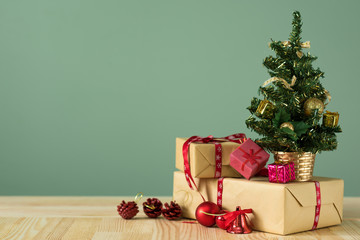 Christmas background. A small Christmas tree and boxes with gifts on a wooden table. Green background. Space for text. New Year's background.