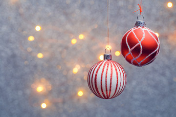 Image of Christmas red balls with pattern on gray background with burning lights.