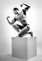 athletic guy - bodybuilder,   pose on gray background