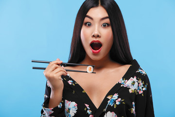 Surprised Asian woman eating sushi and rolls on a blue background. Black Friday sushi sale.