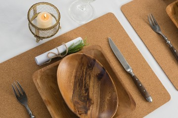 Wooden plate and cutlery set on a table