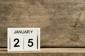 White block calendar present date 25 and month January on wood background