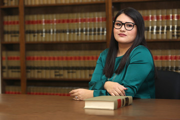 Woman lawyer in law library, portrait of a young attractive female Hispanic lawyer.