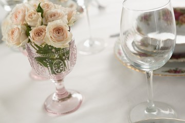 Wine glass and flowers set on a dining table