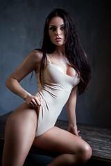 Beautiful black hair woman in beige bodysuit posing at camera against grey background