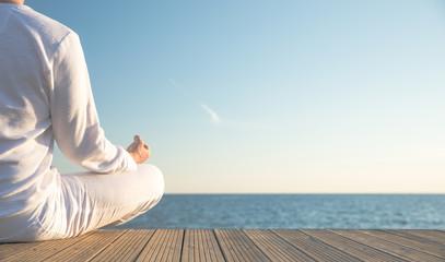 Junger Mann macht Yoga Position am Strand. Sonnenuntergang. Wunderschöner Blick aufs Meer Wall mural