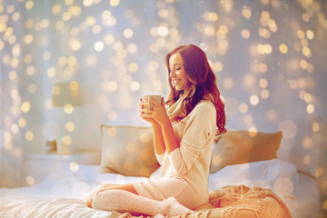 Fototapete - happy woman with cup of coffee in bed at home