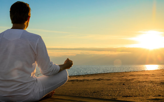 Young sexy man is doing yoga workout exercises at a beautiful beach sunset. looking at the ocean landscape. sundown