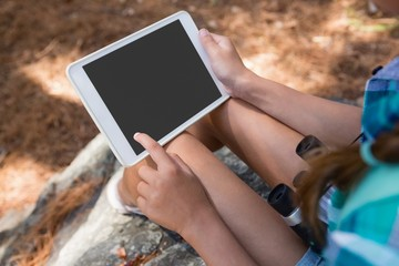 Close-up of girl holding digital tablet in the forest