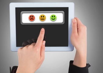 Hands holding tablet with feedback smiley satisfaction icons