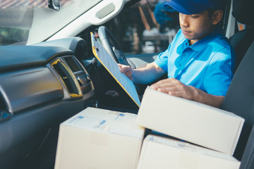 Young Delivery Man Checking Customer List On Clipboard.