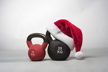 A large black Kettlebell wearing a red  Santa hat next to a smaller red kettle bell on a plain light grey background