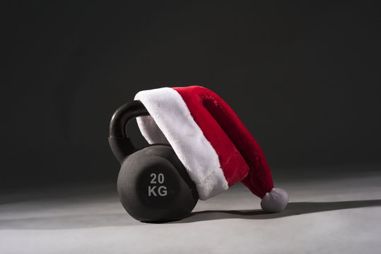 A black Kettlebell with a red and white Santa hat on a plain black background