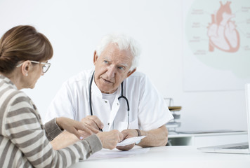 Elderly cardiologist consulting tests results