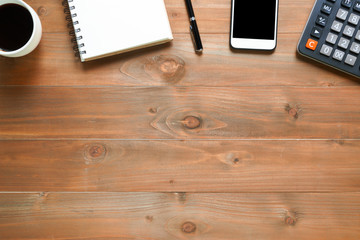 Top view of blank notepad on wooden office desk with smartphone, calculator and coffee cup.