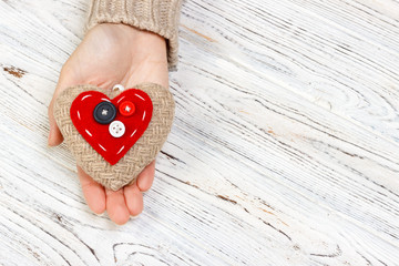 red heart in hands closeup on wooden background. Valentine's Day concept with copyspace