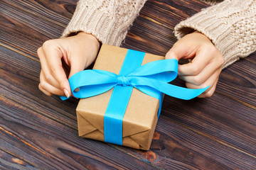 Woman hands give wrapped valentine or other holiday handmade present in paper with blue ribbon. Present box, decoration of gift on white wooden table, top view with copy space